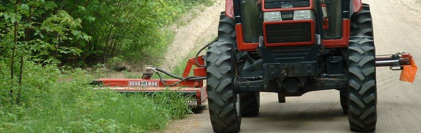 Photo of tractor doing roadside mowing.