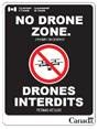 image of signage posted at airport stating that the area is a no drone zone